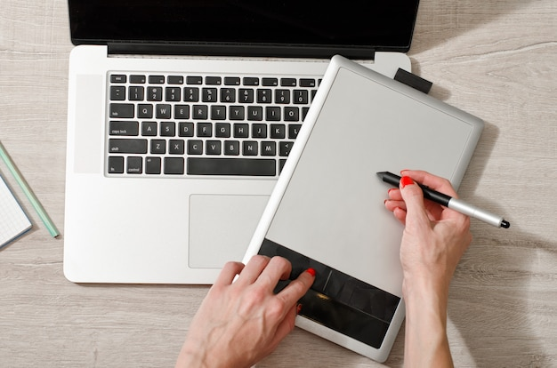 Female hand with a stylus on a graphic tablet, laptop open on a light table, top view