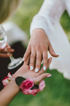 Female hand with wedding ring, bridesmaids