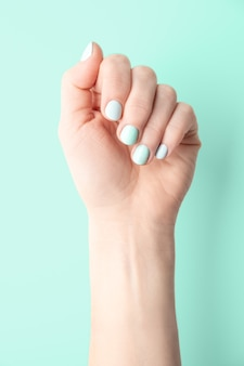 Female hand with well-groomed and painted nails on a green background