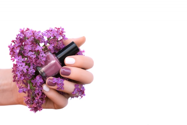 Женская рука с белым и фиолетовым дизайном ногтей держит сиреневые цветы