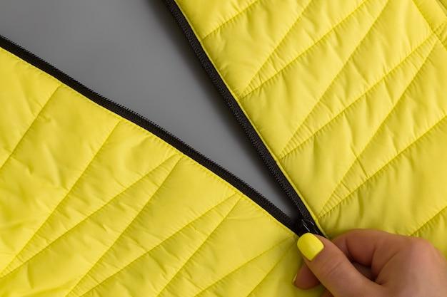 노란색 매니큐어와 여성 손은 회색 바탕에 노란색 재킷의 지퍼를 풉니 다. 2021 년 올해의 색상, 일루미 네이 팅 및 얼티미트 그레이