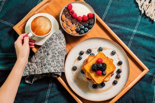 ベッドでの朝食時にヨーグルトボウルとベリー、フレンチトースト、プレート上のコーヒーカップと女性の手