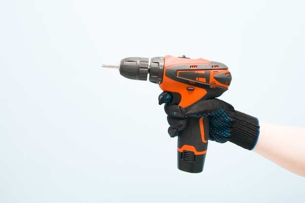 A female hand in a working rubberized black glove is cutting a screwdriver on a light background