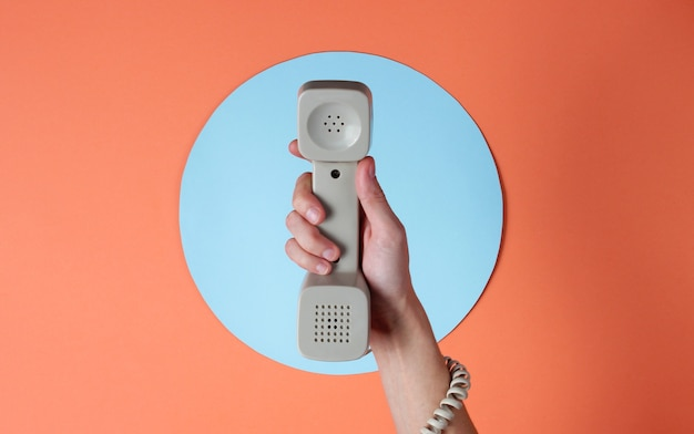 Женская рука, обернутая кабелем, держит телефонную трубку кораллового цвета с синим кругом