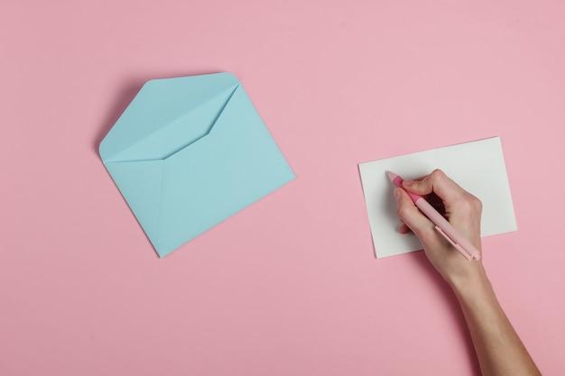Женская рука пишет письмо ручкой на розовом фоне пастельных тонов. свадебные приглашения, любовное письмо, валентинка. вид сверху