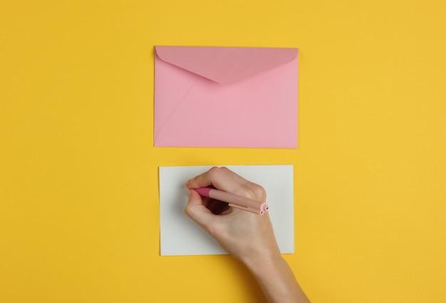 Женская рука пишет письмо ручкой на желтом фоне. свадебные приглашения, любовное письмо, валентинка. вид сверху