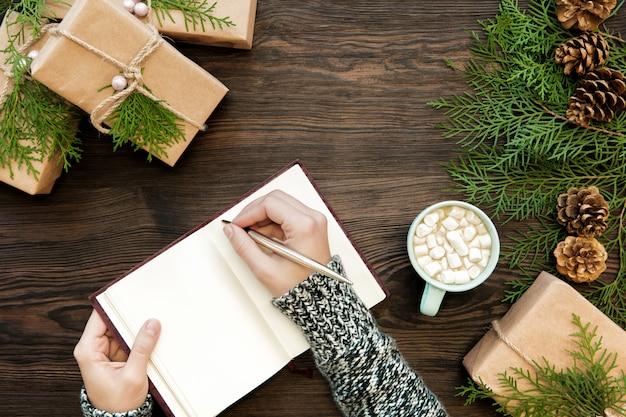 여성 손 선물 및 전나무 콘 어두운 보드에 노트북에 크리스마스 편지를 씁니다