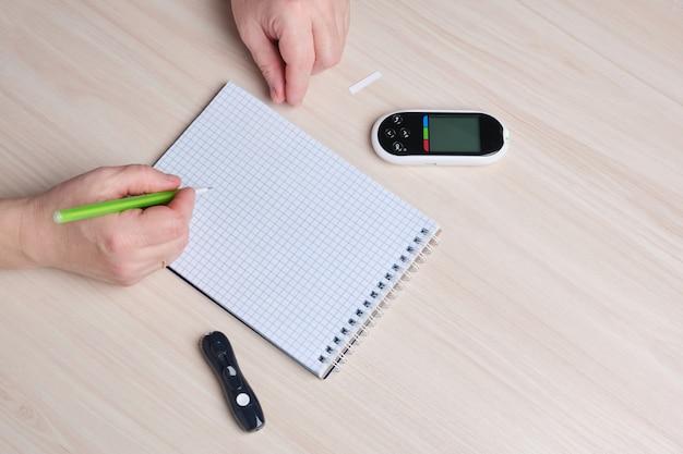 Женская рука записывает показания глюкометра в блокноте, концепция контроля диабета и сахара в крови