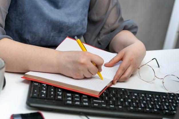 여성의 손은 직장에서 노트북에 씁니다. 작업 관리자. 작업 예약. 직장에서 회계사입니다.