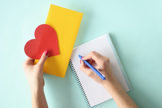 Female hand writes letter in a notebook and holds valentine card with an envelope in her hands