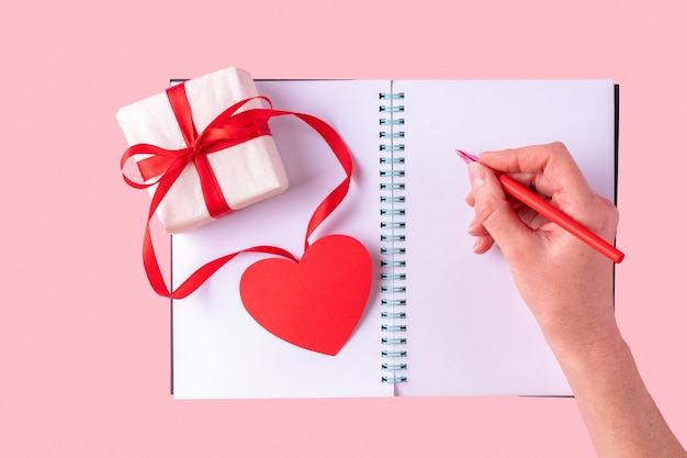Female hand writes a love message with a red pen in a white blank open notebook
