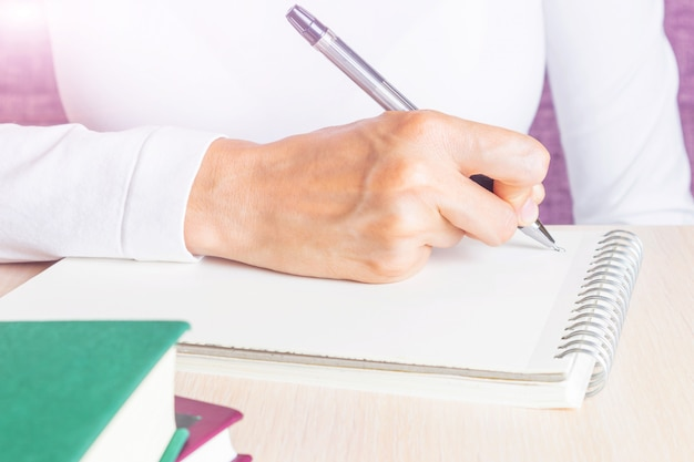 Female hand writes in notebook by pen.