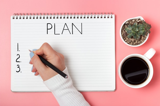Female hand writes in notepad of plan on a pink background