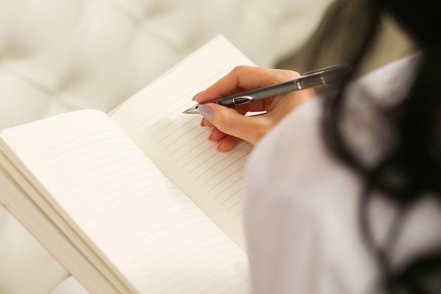 Женская рука пишет заметки в блокноте.