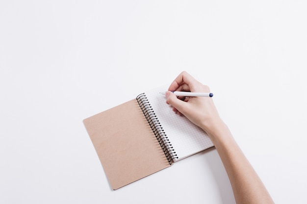 Female hand writes a pen in a notebook on a white table