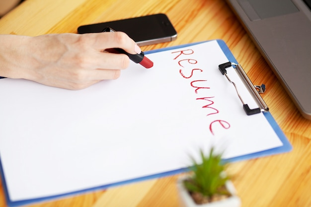 Female hand writes resume with lipstick on white sheet of paper.