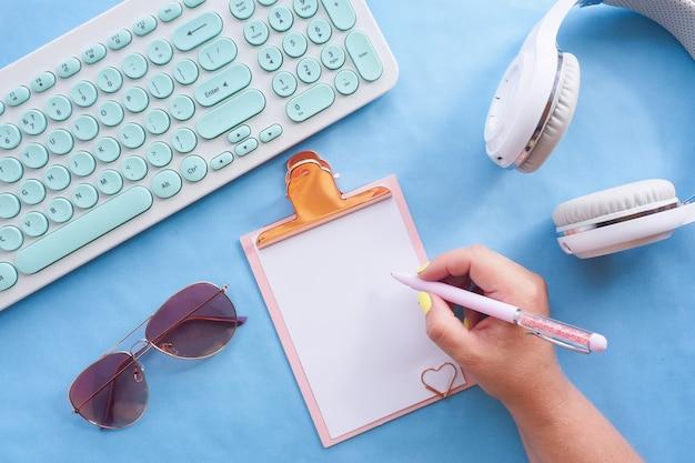 Женская рука пишет ручкой в буфер обмена, наушники, солнцезащитные очки и клавиатуру на синем.