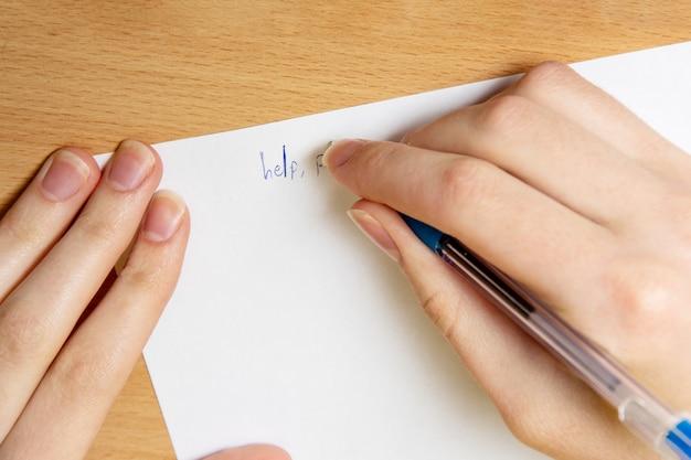 Женская рука пишет ручкой на белом листе. помогите, крупным планом. понятие насилия.