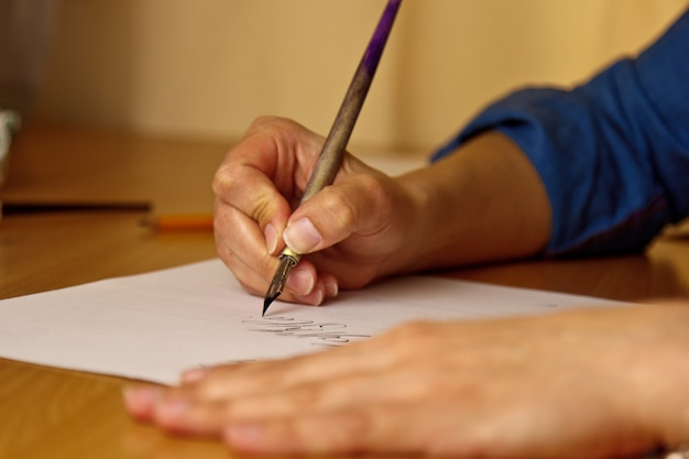Female hand writes with the inky pen on a white paper sheet with stripes.