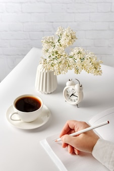A female hand writes with a pencil in a notebook lying on a white table next to a cup of hot coffee and a vase of lilac flowers.