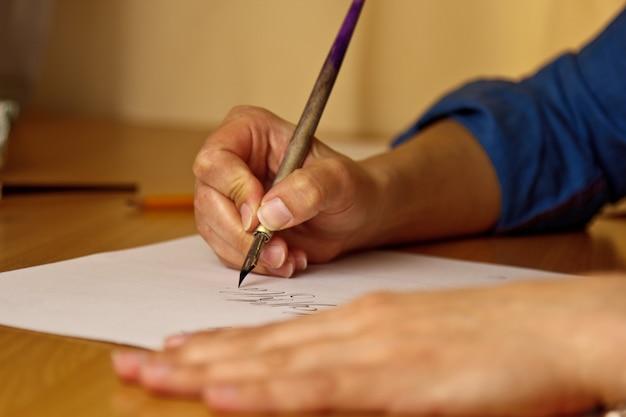 여성 손 줄무늬와 흰 종이 시트에 더러워진 펜으로 씁니다.