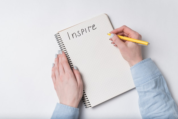 Female hand writes word inspire in copybook. notepad and pen, white background