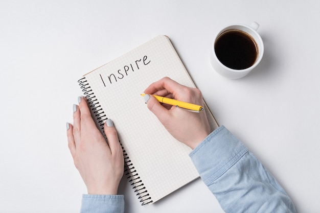 Female hand writes words inspire in copybook. notepad, pen and coffee on white