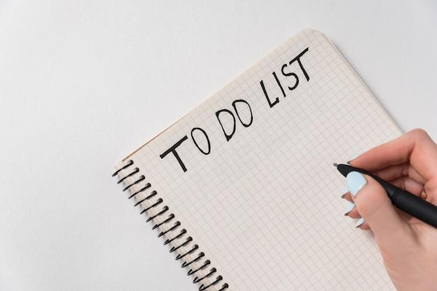 할 일 목록을 작성하는 여성 손. 흰색 바탕에 노트북입니다. 일 월에 대한 계획