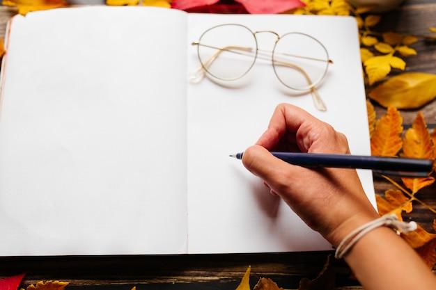 Женская рука, пишущая в пулевом журнале. чистая страница блокнота с женщинами объезжает очки на вершине в удобном месте с оранжевыми, желтыми и красными осенними листьями на деревянном столе.