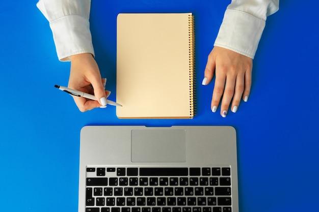 ノートパソコンでテーブルの上のノートに書く女性の手