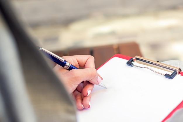 屋外の紙のシートに書く女性の手