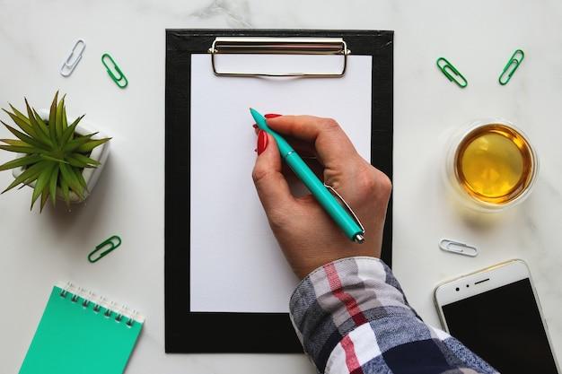 紙でクリップボードに書く女性の手書き