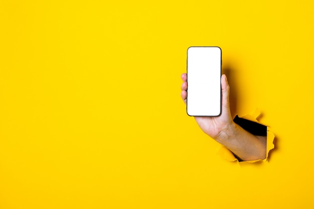 Female hand on a yellow background holding vertical phone, white display