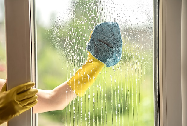 A female hand in a yellow glove washes a dirty window in the summer. rag in hand. cleaning of the apartment.