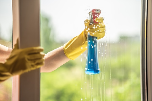 A female hand in a yellow glove washes the window in summer. rag in hand. house cleaning