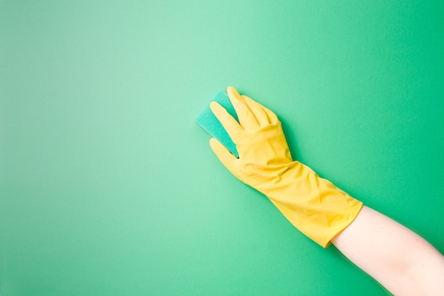 A female hand in a yellow rubber glove washes a plain surface with a green paralon sponge for washing dishes and cleaning on green surface