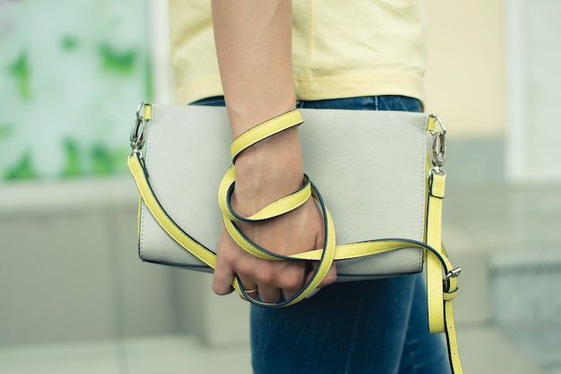 Female handbag gray-yellow in female hands closeup