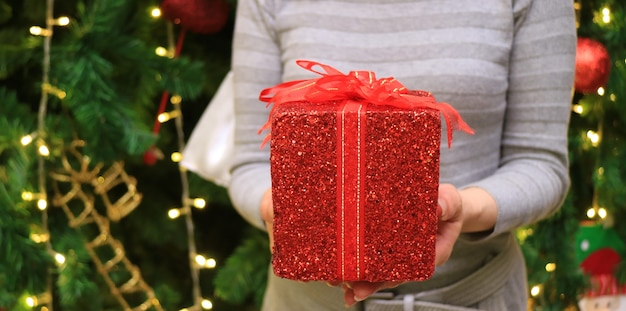 Female handing a red glitter square shape gift box wrapped with red ribbon bow to someone