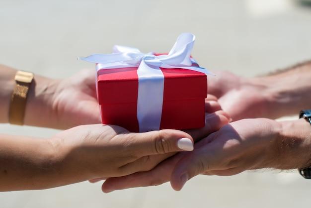 Женские руки принимают подарок из мужских рук. на улице дарят красный ящик с белым бантом.