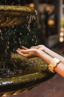 女性の手と水滴がはねかける古代の噴水