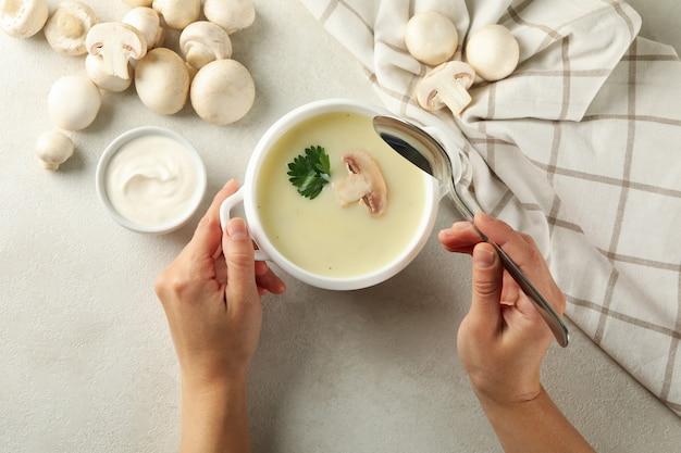 女性の手とおいしいキノコのスープのボウル、上面図