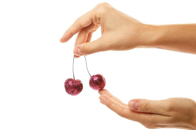 カラフルなきらめきで覆われた女性の手と桜の果実