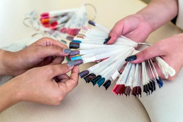 Женские руки и красочная палитра лаков для ногтей