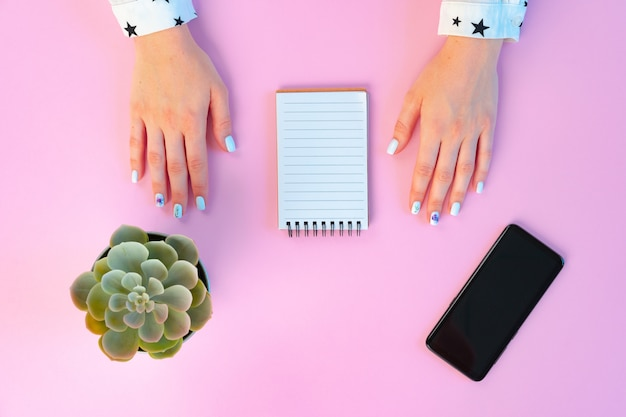 Женские руки и открытый блокнот на розовом виде сверху