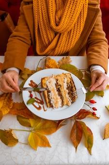 Женские руки и тарелка с тортом на столе с осенними опавшими листьями