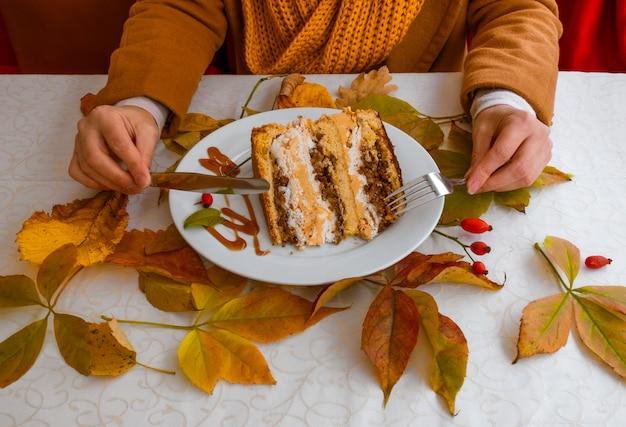 Женские руки и тарелка с тортом на столе с осенними листьями