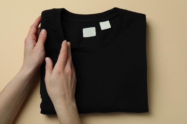 ベージュの背景に女性の手とスウェットシャツ