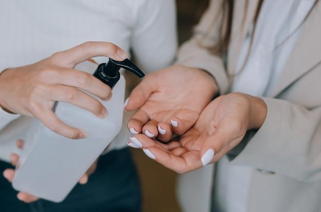 항균 액체 비누를 적용하는 여성 손을 닫습니다.