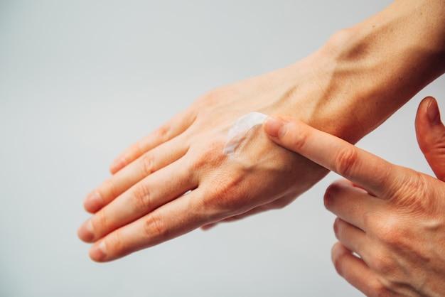 Женские руки, применяя увлажнение
