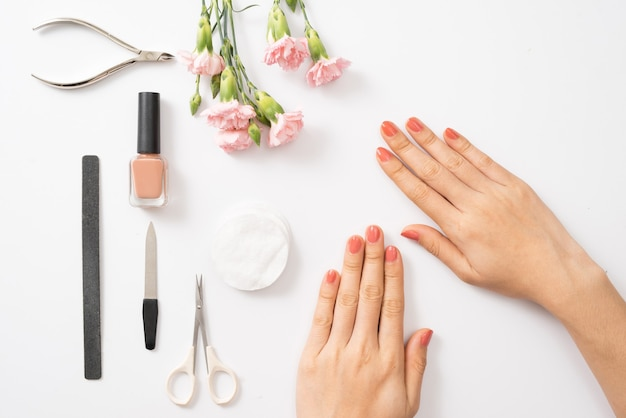 Женские руки, наносящие фиолетовый лак для ногтей на деревянный стол с полотенцем и набором гвоздей